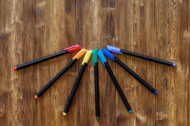 Множество разных маркерных ручек на деревянном столе Premium Фотографии
