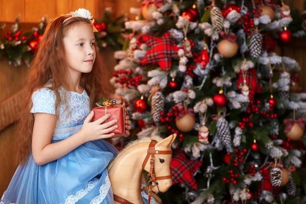 クリスマスツリーの近くのギフトボックスを持つ少女 Premium写真