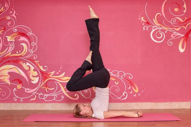 Женщина делает упражнения йоги Premium Фотографии