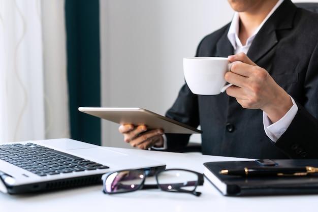 タブレットを押しながら白いコーヒーカップと朝のコーヒーを保持している実業家。 Premium写真