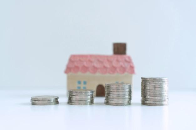 Стопка монет для экономии денег на белом фоне, планы сбережений для жилищной финансовой концепции, крупным планом Premium Фотографии