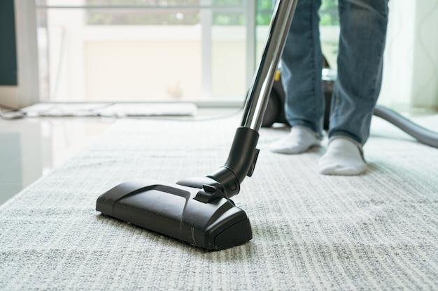 リビングルームで掃除機のクリーニングカーペットを使用している女性。 Premium写真