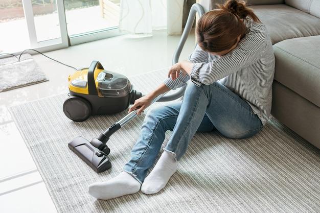 リビングルームで掃除機掃除カーペットを使用した後、床に座っている女性。 Premium写真