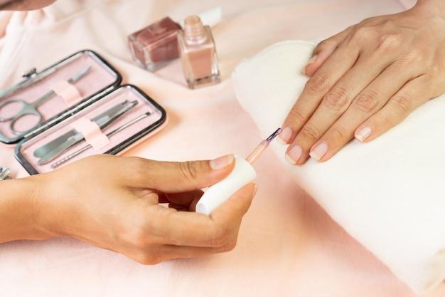 Женские руки делают лак для ногтей в жемчужно-розовом цвете с набором маникюрных инструментов и инструментов на розовом шелковом бархате. красота, концепция маникюра Premium Фотографии