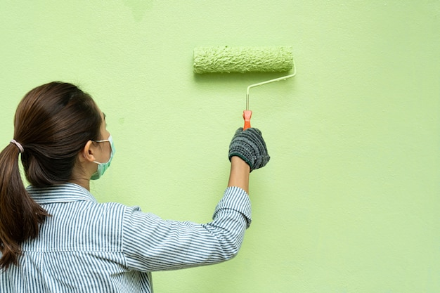 シャツと手袋のペイントローラーで壁を塗る若い女性画家の背面図。 Premium写真