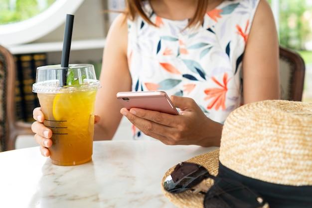カフェで携帯電話を使用しながら飲み物を保持している女性の手のクローズアップ。 Premium写真