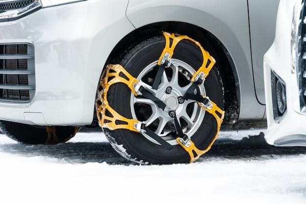 Конец-вверх желтой цепи противоскользящая цепь колеса. на шинах установлены приспособления для обеспечения максимальной тяги при движении по снегу и льду. Premium Фотографии