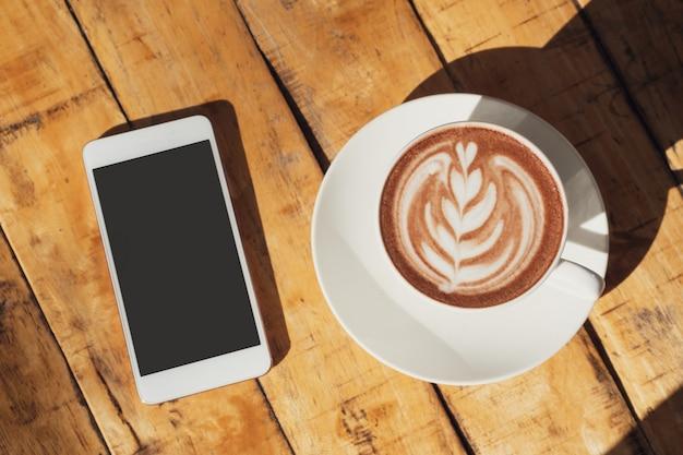 ホットココアまたはチョコレートと木製のテーブル、平面図、コピースペースに携帯電話のカップ。 Premium写真