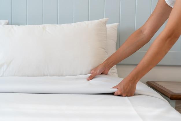 Закройте вверх по руке женщины настроил белую простыню в гостиничном номере, скопируйте космос для текста. Premium Фотографии