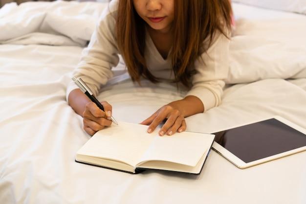 美しい若いアジア女性がベッドの上に敷設し、日記を書きます。ノートブックとタブレットで彼女の手にペンで笑顔のブルネットの女性は脇に置きます。背景にモダンな明るいインテリア。 Premium写真