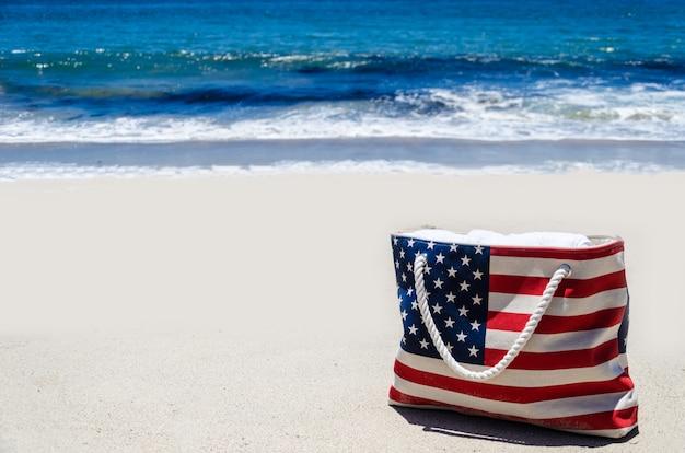 海の近くのアメリカの国旗の色のビーチバッグ Premium写真