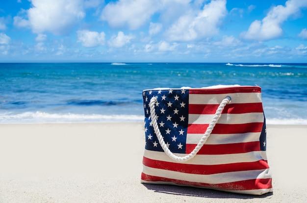 砂浜の海の近くのアメリカの国旗の色のバッグ Premium写真