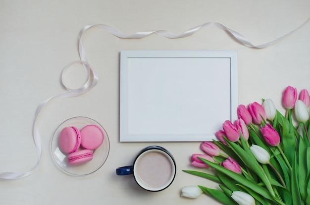 コーヒーカップ、春のチューリップの花、パステルテーブルトップビューの背景にピンクのマカロン Premium写真