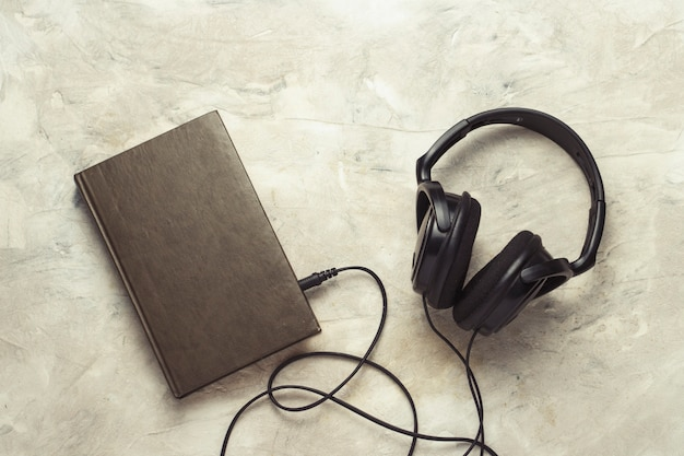 白い石の上に接続された本とヘッドフォン Premium写真