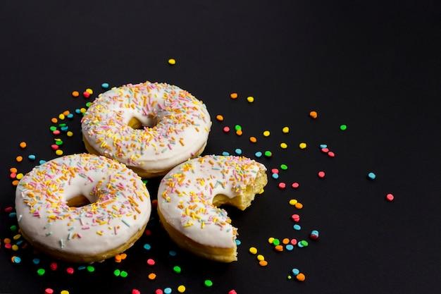 おいしい、甘い、新鮮なドーナツと黒の背景に色とりどりの装飾的なキャンディー。朝食のコンセプト、ファーストフード、コーヒーショップ、パン屋さん。 Premium写真