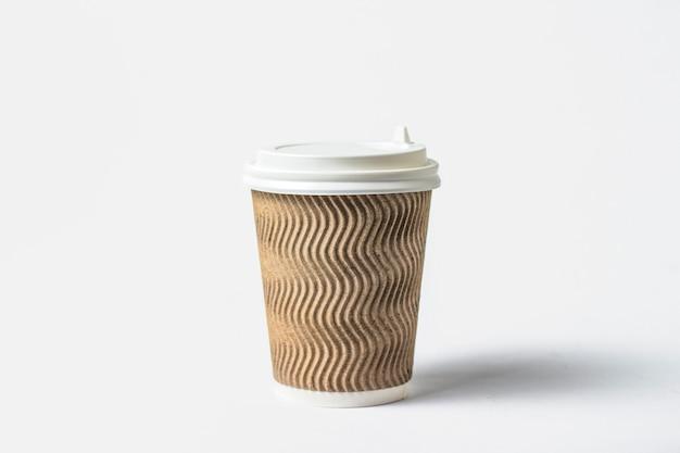 Бумажный стаканчик с защитной крышкой на белом фоне. концепция кофе или чая, фаст-фуд, утренний кофе, завтрак. Premium Фотографии