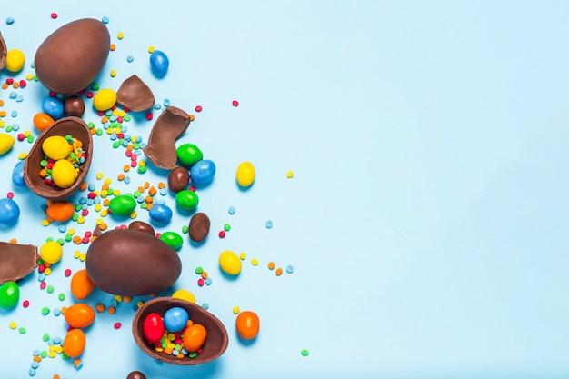 壊れたとチョコレート全体のイースターエッグ、青の背景に色とりどりのお菓子。イースターを祝う概念、イースター装飾、イースターバニーのお菓子を検索します。フラット横たわっていた、トップビュー。コピースペース。 Premium写真