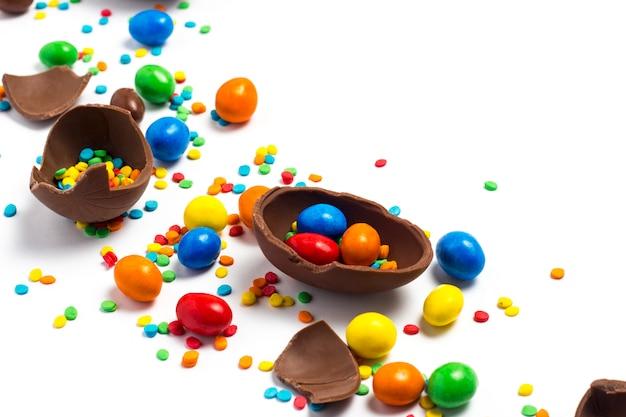 壊れたチョコレートイースターエッグ、白地に色とりどりのお菓子。イースターを祝う概念、イースター装飾、イースターバニーのお菓子を検索します。フラット横たわっていた、トップビュー。コピースペース。 Premium写真