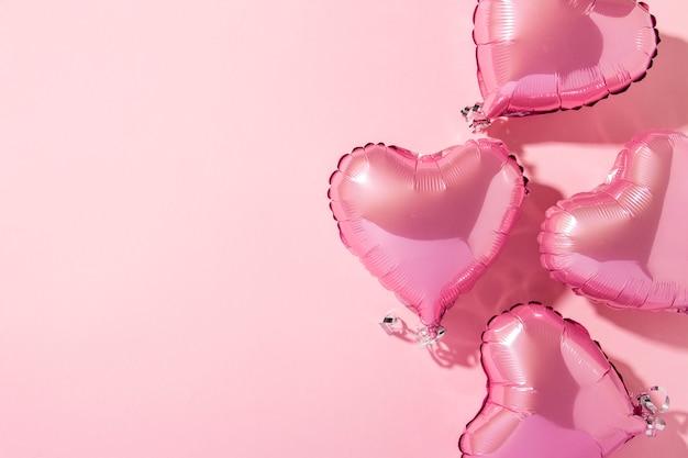 ピンクの背景の気球ハート形。自然光。バナー。愛、結婚式、写真ゾーン。フラット横たわっていた、トップビュー Premium写真