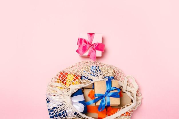 ピンクの表面に贈り物が入ったバッグ。家族、愛する人、クリスマス、バレンタインデーのギフトコンセプト。フラット横たわっていた、トップビュー Premium写真