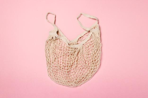 ピンクの表面におしゃれなショッピングバッグ。ショッピング、販売、ショッピング旅行の概念。フラット横たわっていた、トップビュー Premium写真