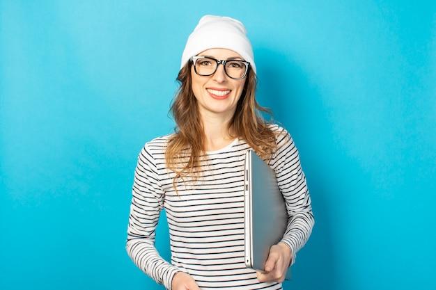 ラップトップ、メガネの女の子、青の白い帽子を保持している若い女の子の笑顔 Premium写真