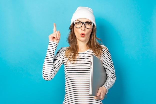 メガネと白い帽子のショックを受けた少女、ラップトップを保持し、青に指を上向き Premium写真