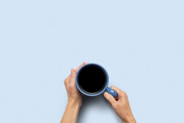 Вручите держать чашку с горячим кофе на голубой предпосылке. концепция завтрак с кофе или чаем. доброе утро, ночь, бессонница. плоская планировка, вид сверху Premium Фотографии