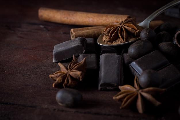 木製の表面にブラックチョコレート、スパイス、ティースプーン Premium写真