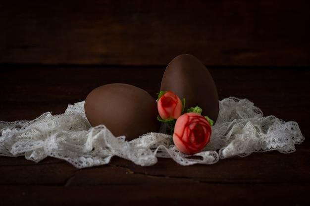Шоколадные яйца, белая кружевная лента, искусственные декоративные розы на темной деревянной поверхности. пасхальная концепция Premium Фотографии