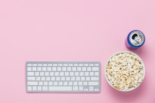 キーボード、ピンクの背景にドリンクとポップコーンのボウルでできます。映画、テレビ番組、ショーをオンラインで視聴するという概念。フラット横たわっていた、トップビュー。 Premium写真