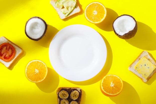 Бутерброды с бананом, помидорами, авокадо, сыром и свежими фруктами, апельсин, кокос и пустая белая тарелка на желтом фоне. концепция здорового завтрака, витамины, диета. плоская планировка, вид сверху. Premium Фотографии