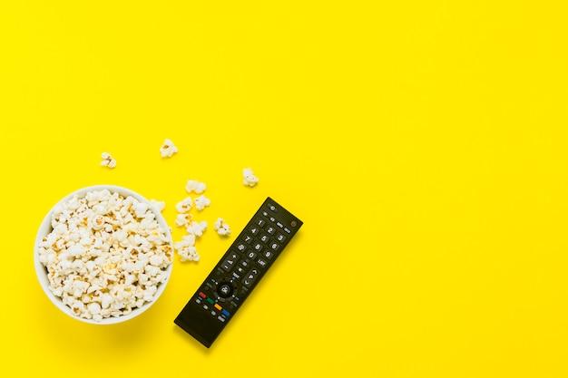 黄色の背景にポップコーンとテレビのリモコンのボウル。テレビ、映画、テレビシリーズ、スポーツ、ショーを観るコンセプト。フラット横たわっていた、トップビュー。 Premium写真