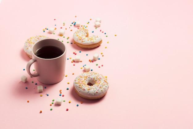 一杯のコーヒー、ピンクの背景に新鮮なおいしい甘いドーナツ。ファーストフード、ベーカリー、朝食、お菓子のコンセプトです。ミニマリズム。フラット横たわっていた、トップビュー、コピースペース。 Premium写真
