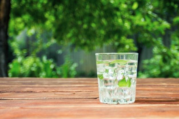 木製のテーブルの上と庭の背景に冷たいさわやかなドリンクとグラスに氷とミントの葉。屋外レクリエーションのコンセプト Premium写真