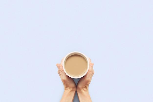 Две руки, держа чашку с горячим кофе на синем фоне. концепция завтрак с кофе или чаем. доброе утро, ночь, бессонница. плоская планировка, вид сверху Premium Фотографии