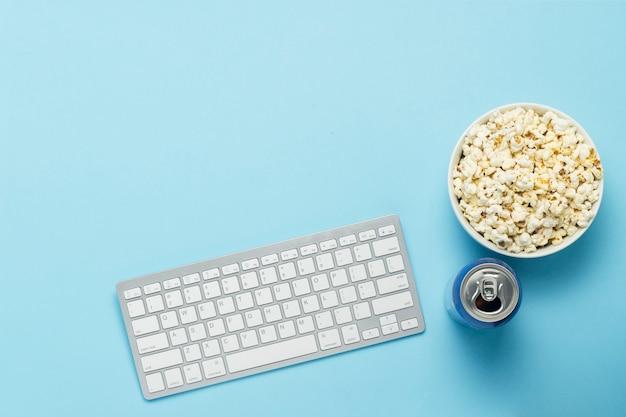 キーボードとブリキ缶、ドリンク、栄養ドリンク、青色の背景にポップコーンのボウル。映画、テレビ番組、スポーツイベントをオンラインで見るというコンセプト。フラット横たわっていた、トップビュー Premium写真