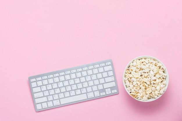 キーボードとピンクの背景のポップコーンのボウル。映画、テレビ番組、ショーをオンラインで視聴するという概念。フラット横たわっていた、トップビュー。 Premium写真