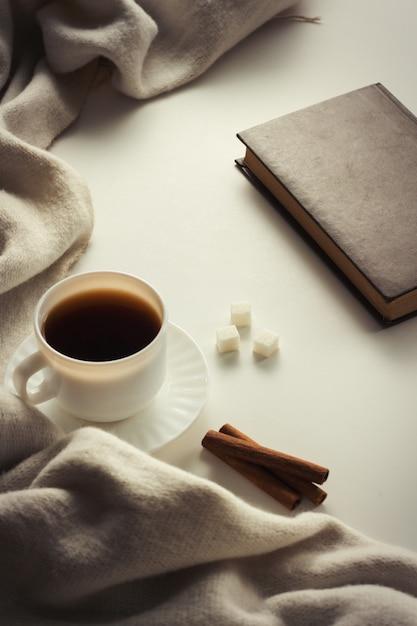 Чашка с кофе, шарф, книга на белой поверхности Premium Фотографии