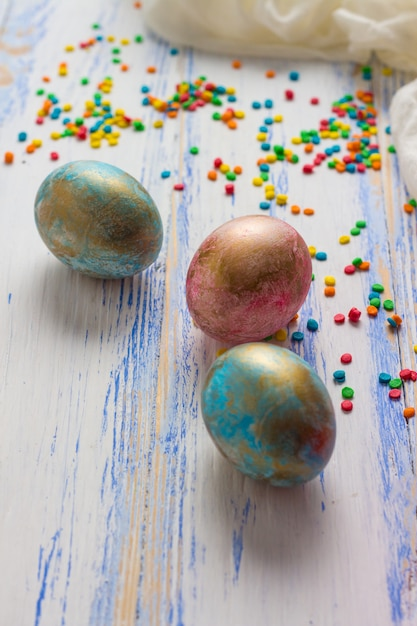 Пасхальные яйца, сладости, белая ткань на белом деревянном столе. пасхальная концепция Premium Фотографии