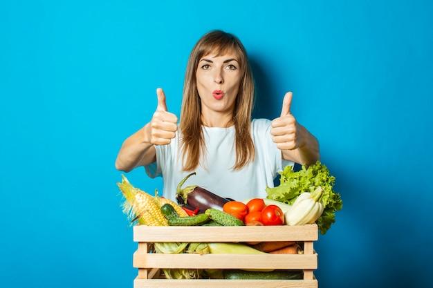 Молодая женщина с удивленным лицом держит коробку со свежими овощами на синем. хорошая концепция урожая, натуральный продукт Premium Фотографии