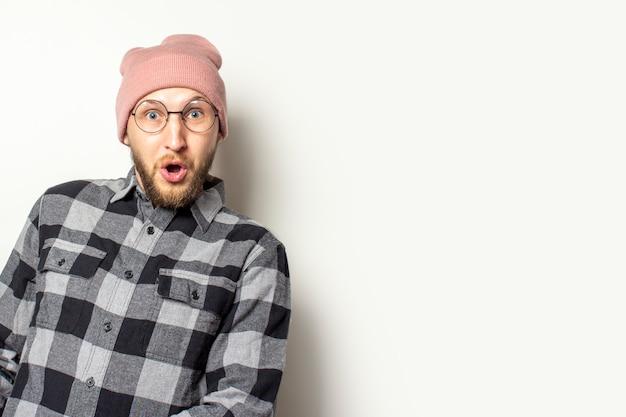 ひげ、格子縞のシャツとメガネの若い男は、孤立した白の驚いた顔で側から外を見てください。ジェスチャーサプライズショック Premium写真