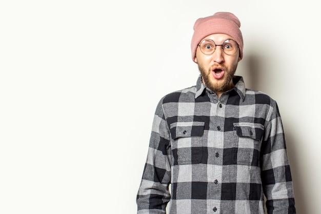 帽子、格子縞のシャツ、孤立した白の驚いた顔でメガネのひげを持つ若い男。驚き、衝撃のジェスチャー Premium写真