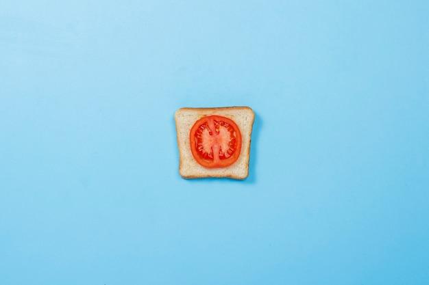 Сэндвич с помидорами на синей поверхности. концепция диеты, здорового питания, похудения. плоская планировка, вид сверху. Premium Фотографии
