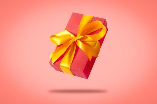 明るいピンクの表面に飛んでいるギフトボックス。休日の概念、ギフト、販売、結婚式、誕生日。 Premium写真