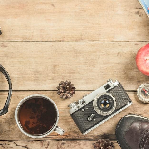 Сапоги, металлическая чашка с чаем, компас и другие атрибуты для похода по деревянной поверхности. Premium Фотографии