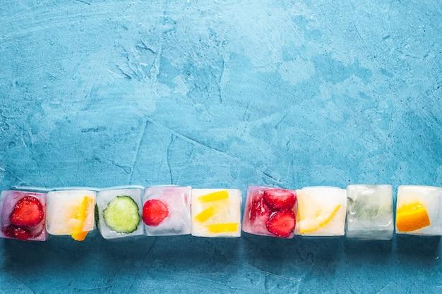 石の青い表面にフルーツのアイスキューブ。ライン。ミント、イチゴ、チェリー、レモン、オレンジ。フラット横たわっていた、トップビュー Premium写真