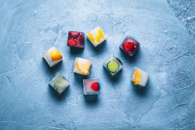 石の青い表面にフルーツのアイスキューブ。ミント、イチゴ、チェリー、レモン、オレンジ。フラット横たわっていた、トップビュー Premium写真