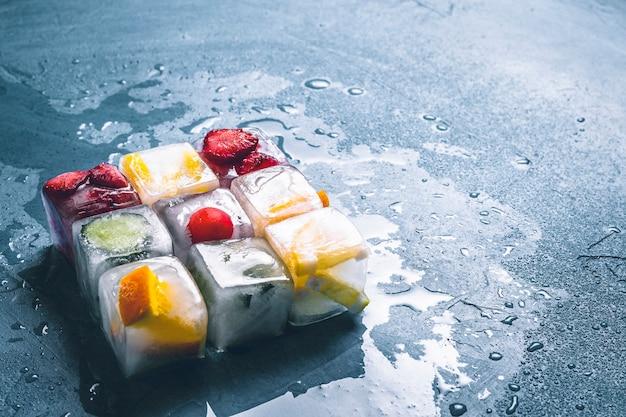 石の青い表面にフルーツのアイスキューブ。正方形の形状。ミント、イチゴ、チェリー、レモン、オレンジ。フラット横たわっていた、トップビュー Premium写真