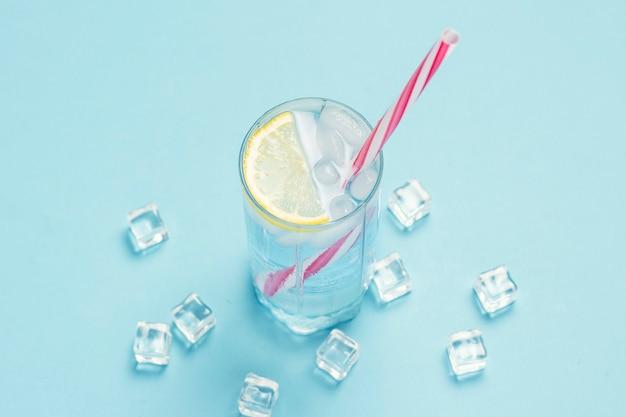 水や氷と氷と青い表面にレモンと飲み物のグラス。暑い夏、アルコール、冷たい飲み物、喉の渇きを癒す概念。フラット横たわっていた、トップビュー Premium写真